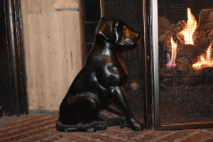 Small black dog sculpture next to fireplace.